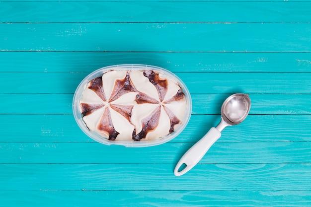 Eiscreme im behälter mit löffel auf holzoberfläche