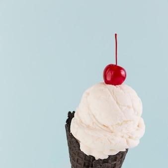 Eiscreme im schwarzen kegel mit kirsche oben