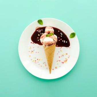Eiscreme im waffelkegel mit sirup und streuseln