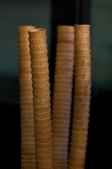 Eiscreme-kegel-stapel auf dunklem hintergrund. vertikale aufnahme