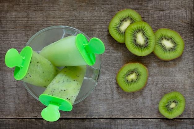Eiscreme mit kiwi und fruchteis gegen einen hölzernen weinlesehintergrund, kopienraum. das konzept einer gesunden ernährung und entgiftungsdiät.