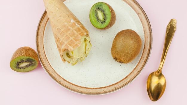 Eiscreme nahe löffel und kiwi auf platte