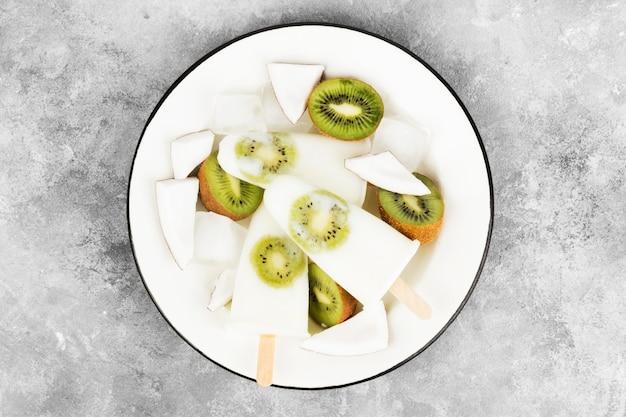 Eiscreme vom joghurt / von der kokosmilch von der kiwi auf einem hellen hintergrund