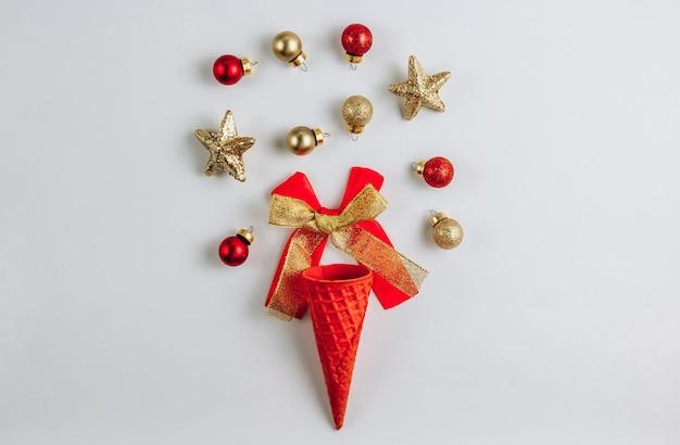 Eiscreme-waffel-kegel mit weihnachtskugeln auf weißem hintergrund. draufsicht. flach liegen