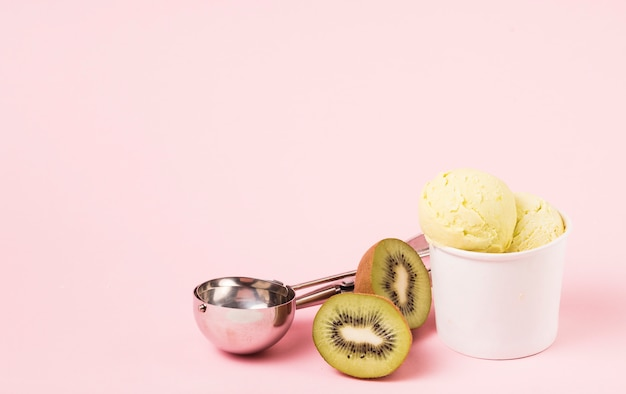 Eiscremebälle in der schale nahe kiwi und schaufel