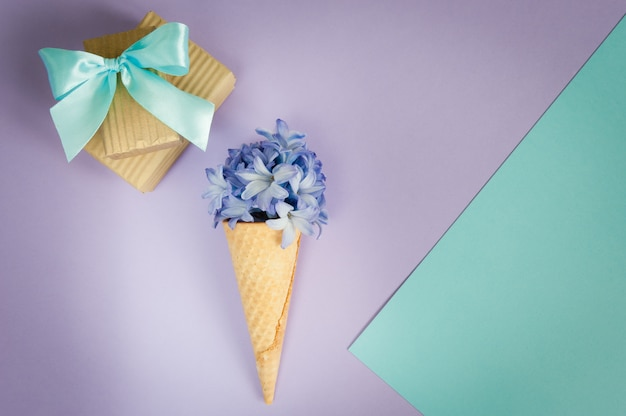 Eiscremehorn oder -kegel mit purpurroter hyazinthe auf einem purpur - tadelloser hintergrund.