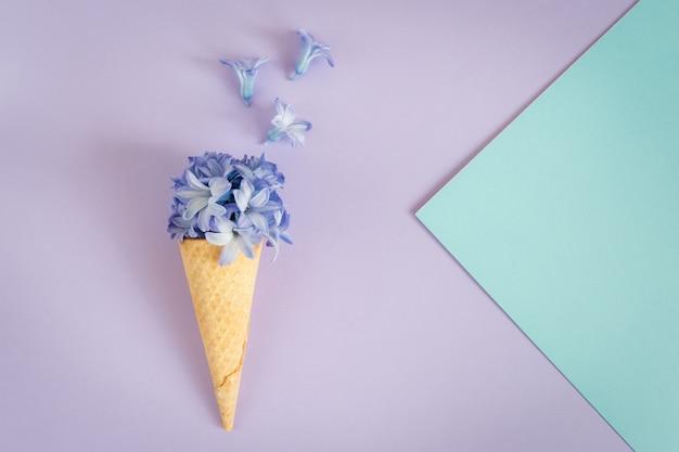 Eiscremehorn oder -kegel mit purpurroter hyazinthe auf einem purpurroten hintergrund.