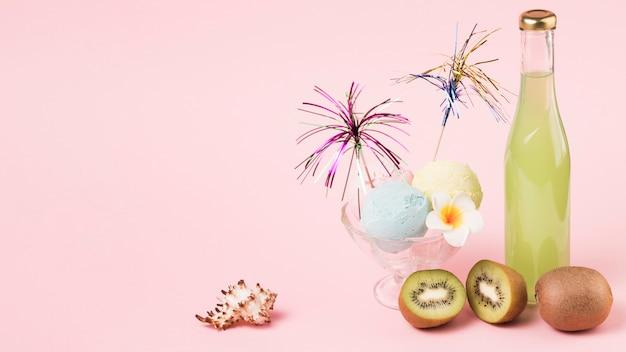 Eiscremekugeln mit dekorativem stab auf glasschüssel nahe früchten und flasche