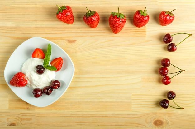 Eisdessert mit erdbeeren und kirschen in einem teller