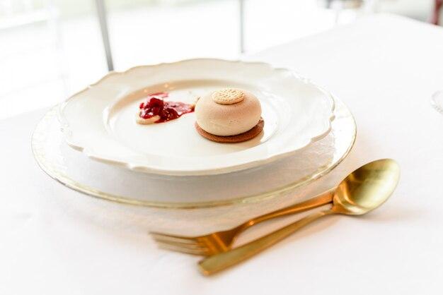 Eisdessert mit keks und roter fruchtmarmelade elegant präsentiert mit goldenem besteck