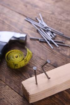 Eisen, zentimeterband und nägel auf holztisch hämmern