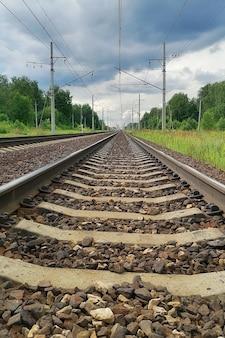 Eisenbahn in einer ländlichen landschaft. abend, sommerzeit, bewölkter himmel, vertikales foto