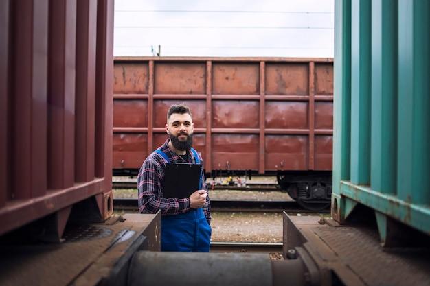 Eisenbahnarbeiter, der durch züge steht und zur kamera am bahnhof schaut