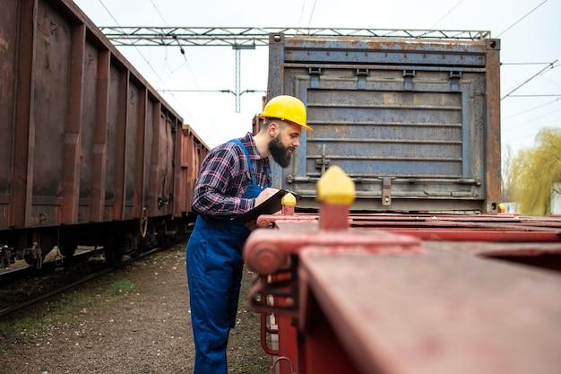 Eisenbahnarbeiter, der eisenbahnwaggons am bahnhof überprüft