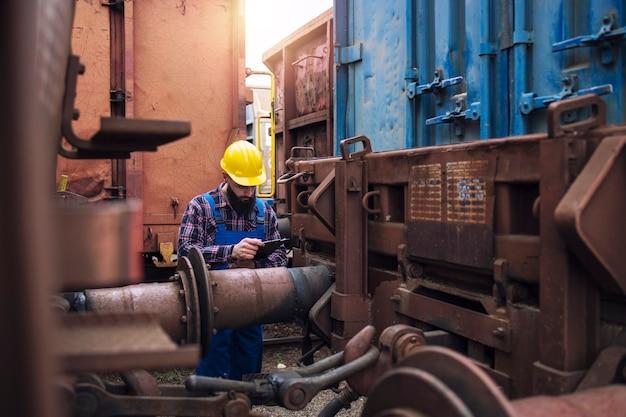 Eisenbahnarbeiter, der frachtcontainer am güterbahnhof überprüft