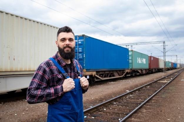 Eisenbahnarbeiter, der stolz am bahnhof steht