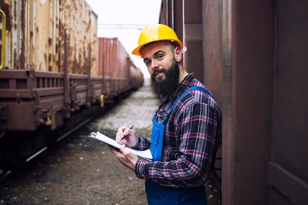 Eisenbahnarbeiter mit zwischenablage, die durch die versandbehälter steht und nach vorne schaut