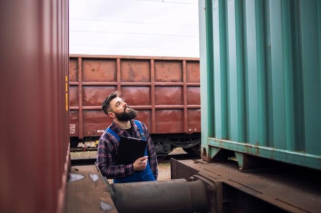 Eisenbahnarbeiter-supervisor, der schiffsfrachtcontainer am güterbahnhof inspiziert