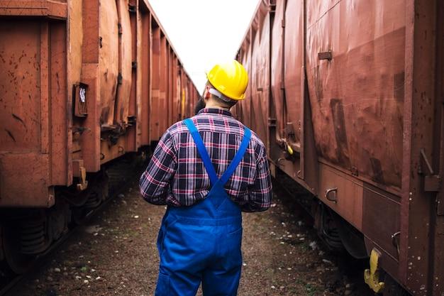Eisenbahnaufseher, der zwischen eisenbahnwaggons geht und fracht auf reedereien überprüft