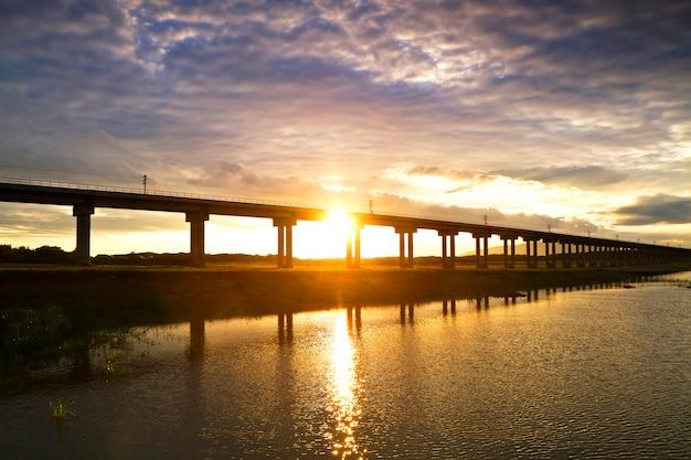 Eisenbahnbrücke über der verdammung während des sonnenuntergangs, bahnstrecken in das reservoir, pa sak jolasid dam, lopburi, thailand