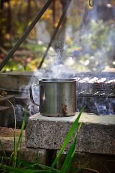 Eisenbecher mit heißem getränk in der nähe von feuer
