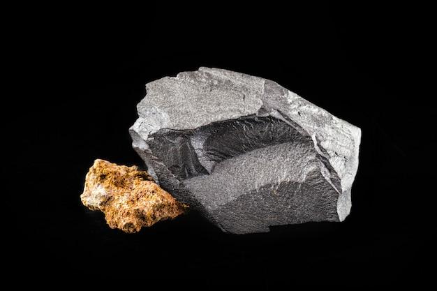 Eisenerz und bauxit auf isolierter schwarzer oberfläche, erze, die in der gießereiindustrie verwendet werden