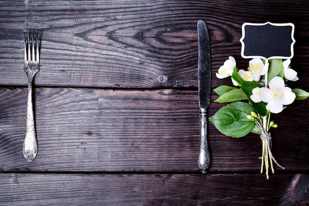 Eisengabel und messer mit einem bouquet von jasmin
