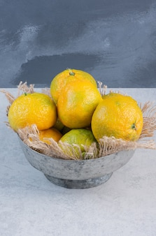 Eisenschale voll von mandarinen (orangen, clementinen, zitrusfrüchten) über grauem hintergrund.