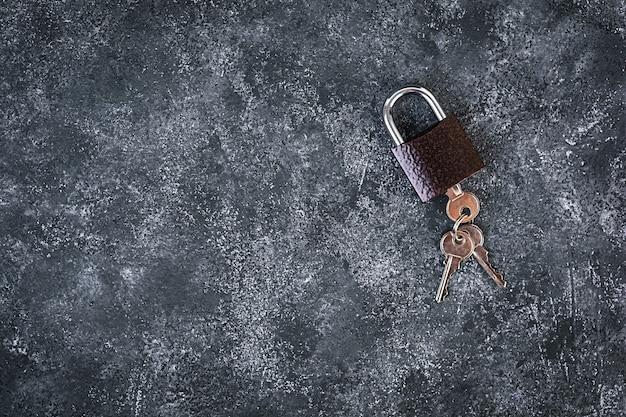 Eisenschloss mit schlüsseln auf grauem hintergrund. draufsicht.