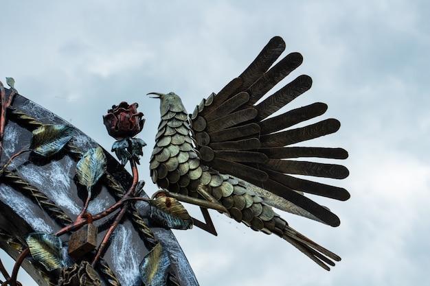 Eisenskulptur eines vogels vor dem hintergrund eines beeindruckenden himmels hoffnung und stärke atmosphärisches foto...