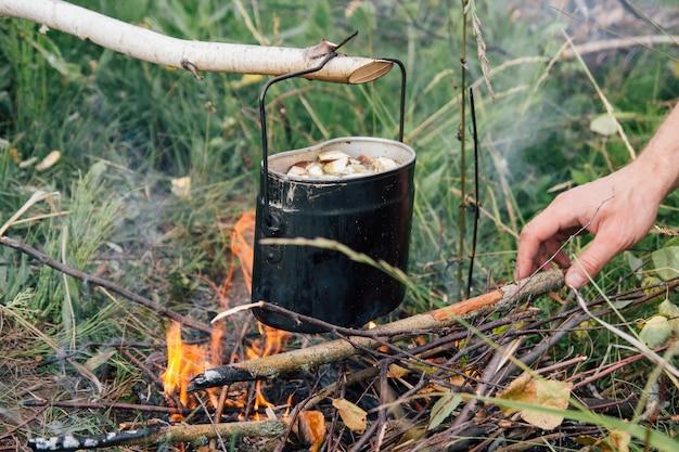 Eisentopf kocht suppe über offenem feuer auf einem campingplatz