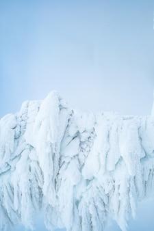Eisfiguren unter großer eis- und schneemenge auf hellblauem hintergrund