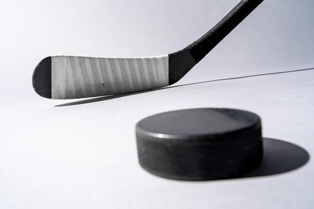 Eishockey-puck und hockeyschläger auf lokalisiertem weißem hintergrund