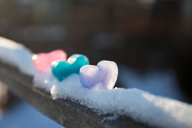Eisige farbige herzen auf schnee, valentinstagskarte