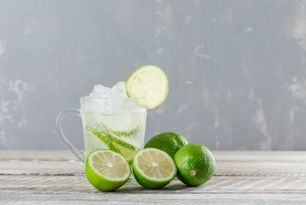 Eisiger mojito-cocktail mit limetten in einer glasschale auf holz- und gipshintergrund, seitenansicht.