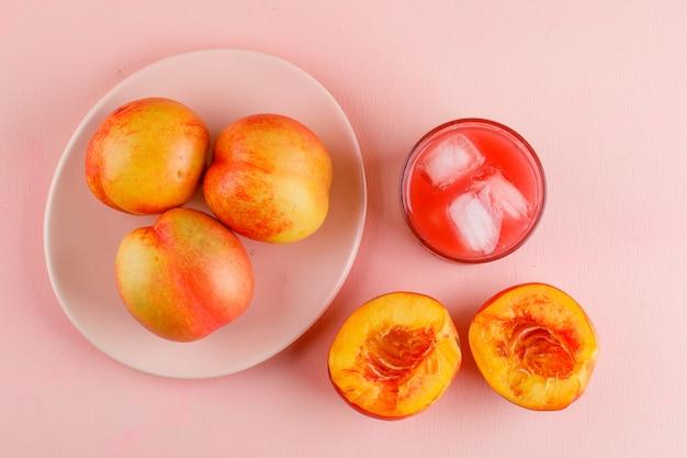Eisiger saft in einem glas mit flachen nektarinen lag auf einer rosa oberfläche