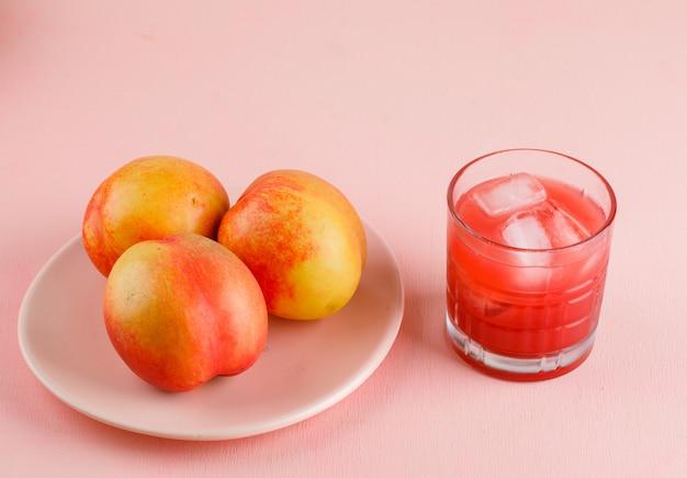 Eisiger saft in einem glas mit nektarinen-hochwinkelansicht auf einer rosa oberfläche