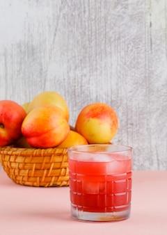 Eisiger saft in einem glas mit seitenansicht der nektarinen auf rosa und grungy wand