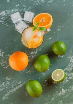 Eisiges entgiftungswasser in einer tasse mit orangen, minze und limetten lag flach auf einer gipsoberfläche