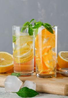 Eisiges entgiftungswasser in glas mit orange, zitrone, minze, schneidebrett-nahaufnahme auf grunge und grauer wand