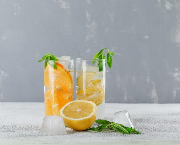 Eisiges entgiftungswasser mit orange, zitrone, minze im glas auf gips und schmutzhintergrund, seitenansicht.