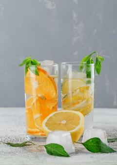 Eisiges entgiftungswasser mit orange, zitrone, minze im glas auf gips und schmutzwand, seitenansicht.