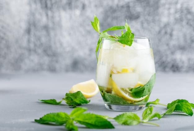 Eisiges entgiftungswasser mit zitrone und minze in einem glas auf grauer und schmutziger oberfläche