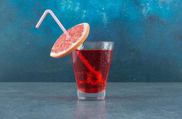 Eisiges glas saft, geschmückt mit einem strohhalm und einer frischen grapefruitscheibe auf blauem hintergrund. foto in hoher qualität