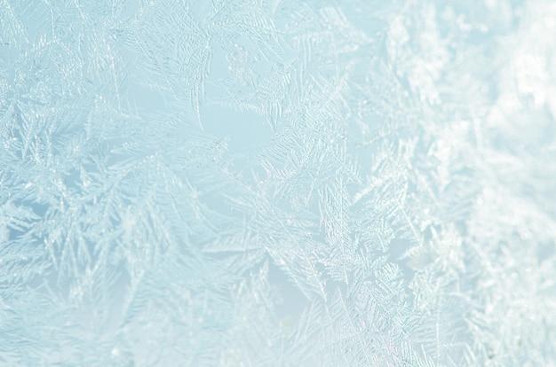 Eisiges natürliches muster auf winterfenster.