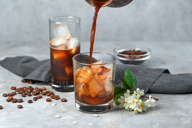 Eiskaffee an einer grauen wand zubereiten. kaffee in ein glas mit eis gießen. seitenansicht.