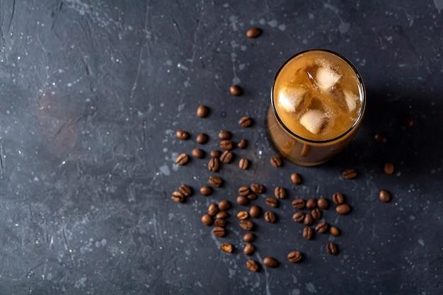 Eiskaffee frappe in hohem glas. kühles sommergetränk auf einem dunklen hintergrund in zurückhaltendem.
