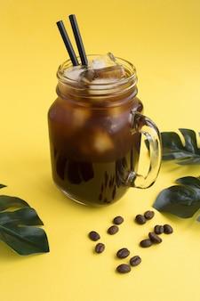 Eiskaffee im glas auf dem gelben hintergrund