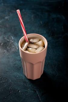 Eiskaffee in einem glas auf einer dunkelblauen steinoberfläche. konzeptkühlgetränk, durst, sommer, kolabaum mit eis. flach lag, ansicht von oben