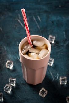 Eiskaffee in einem glas auf einer dunkelblauen steinoberfläche mit eiswürfeln. konzept kühlen getränk, durst, sommer, cola mit eis, nachtleben, club. flachgelegt, draufsicht